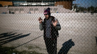 A migrant stands behind a fence outside a temporary housing facility for migrants located in a former Olympic hall in Faliro suburb of Athens, on December 13, 2015. The venue houses mainly African and Iranian migrants, who were transfered earlier this week from Greece's borders with Macedonia, which allows only Syrians, Afghans and Iraqis through. All are trapped in Greece as economic migrants by EU refugee rules, and desperate to get out. Greece said it would seek to deport economic migrants, who had been blocked at its border with Macedonia after Skopje clamped down on entry, if they are not entitled to asylum. / AFP / ANGELOS TZORTZINIS        (Photo credit should read ANGELOS TZORTZINIS/AFP/Getty Images)
