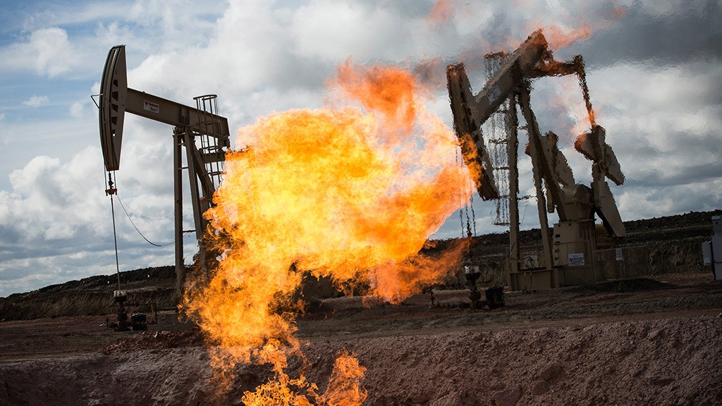 WILLISTON, ND - JULY 26:  A gas flare is seen at an oil well site on July 26, 2013 outside Williston, North Dakota. Gas flares are created when excess flammable gases are released by pressure release valves during the drilling for oil and natural gas. North Dakota has been experiencing an oil boom recently, bringing tens of thousands of jobs to the region, lowering state unemployment and bringing a surplus to the state budget.  (Photo by Andrew Burton/Getty Images)