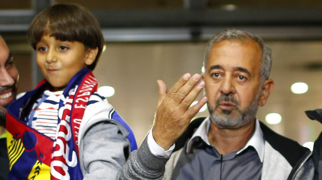 Syrian Osama Abdul Mohsen gestures next to his son Zaid as they arrive at the Barcelona train station on Wednesday, Sept.16, 2015. The Syrian refugee tripped at a border hotspot by a Hungarian journalist in an incident captured on video that generated global outrage will live in a Madrid suburb after a Spanish soccer academy convinced him to take an apartment offer and help to rebuild his life, an official with the school said Wednesday. Osama Abdul Mohsen was on a train expected to arrive in Madrid at midnight Wednesday. (AP Photo/Manu Fernandez)
