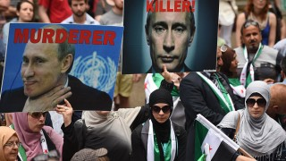 Demonstrators hold up photos of Russian President Vladimir Putin to protest Russia's involvement in the Syrian civil war and in support of refugees and asylum seekers in Sydney on October 11, 2015.  Australia said on October 6, 2015 that it is seeking new countries to resettle refugees in after confirming only four people have moved to Cambodia, which agreed to accept refugees in exchange for aid. AFP PHOTO / Peter PARKS / AFP / PETER PARKS