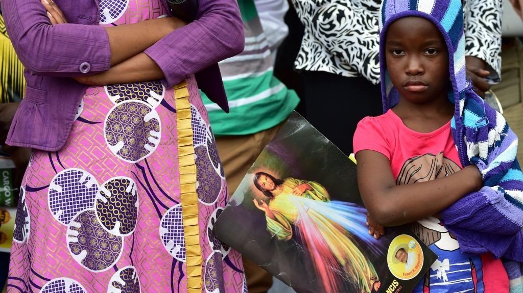 A child waits for the Pope's arrival at Namugongo Martyrs' Shrine for an open air mass on November 28, 2015. Pope Francis arrived in Uganda on November 27 on the second leg of a landmark trip to Africa which has seen him railing against corruption and poverty, with huge crowds celebrating his arrival.  / AFP / GIUSEPPE CACACE