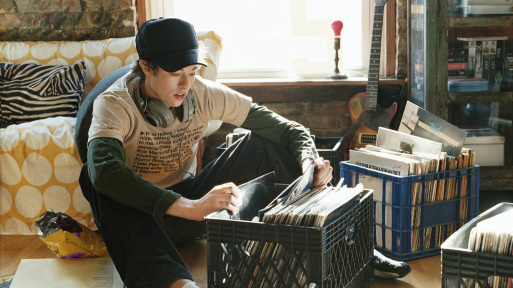 Young Man Sitting in a Cool Apartment Selecting Records From a Crate