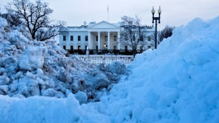 Snow is seen piled in front of the White House as crews clear the area after a snowstorm January 25, 2016 in Washington, DC. The US capital struggled to plow and shovel its way back to life after a blizzard smothered the East Coast, with mountains of snow lining streets, and schools and the federal government shut down. / AFP / Brendan Smialowski