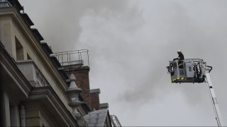 """A firefighter on a platform prepares to reach the site of a fire at the landmark Ritz Hotel in Paris on January 19, 2016. A major fire broke out at the landmark Paris Ritz hotel, which is closed for renovations, the fire service said. The blaze is on the """"top floor of the building and the roof"""", a fire service spokesman said. AFP PHOTO / LIONEL BONAVENTURE / AFP / LIONEL BONAVENTURE"""