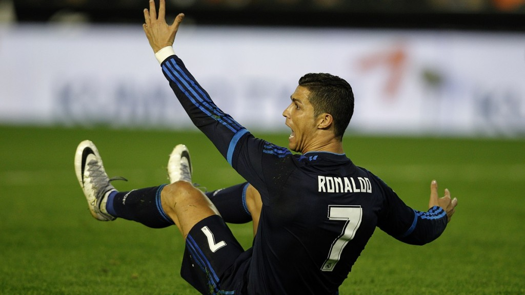 Real Madrid's Portuguese forward Cristiano Ronaldo gestures as he sits on the ground during the Spanish league football match Valencia CF vs Real Madrid CF at the Mestalla stadium in Valencia on January 3, 2016.   AFP PHOTO/ JOSE JORDAN / AFP / JOSE JORDAN
