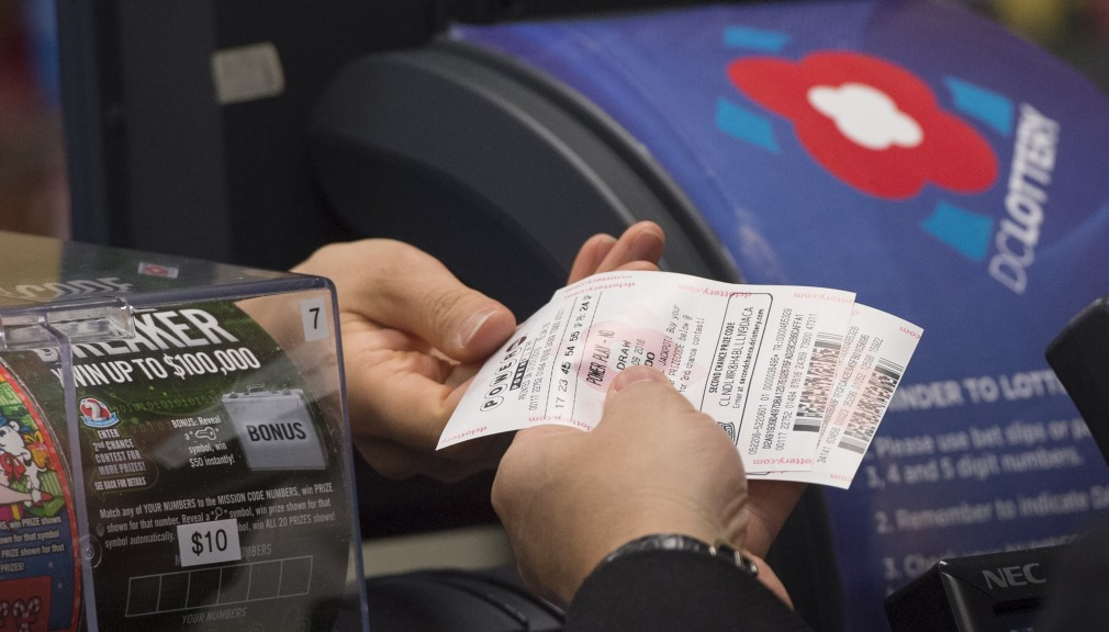 A man purchases a Powerball lottery ticket at a convenience store in Washington, DC, January 7, 2016. Lottery officials predict Saturday's jackpot will reach $700 million, the largest in history. AFP PHOTO / SAUL LOEB / AFP / SAUL LOEB