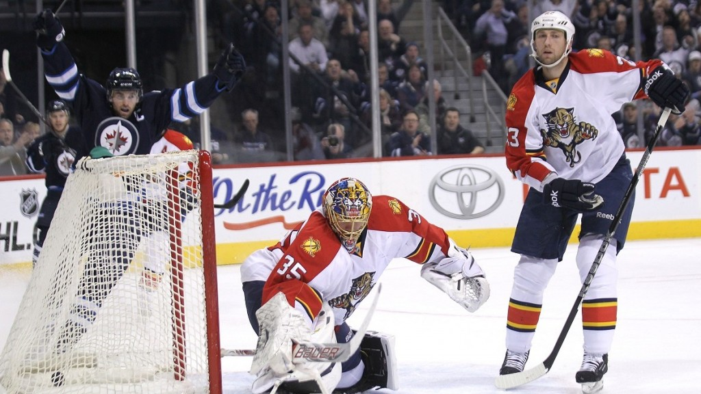 Andrew Ladd (left) of the Winnipeg Jets and Arturs Kulda (right) of the Florida Panthers react as Ladd scores past Jacob Markstrom in the first period at MTS Centre on Thur., April 11, 2013 in Winnipeg, Man. Kevin King/Winnipeg Sun/QMI Agency