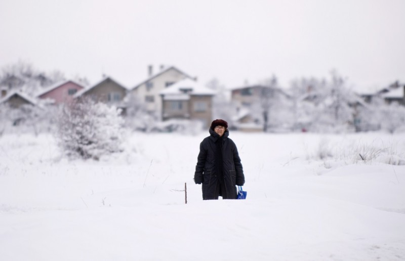 A woman makes her way to a bus stop in a suburb of Sofia after heavy snowfall on January 17, 2016.    / AFP / NIKOLAY DOYCHINOV