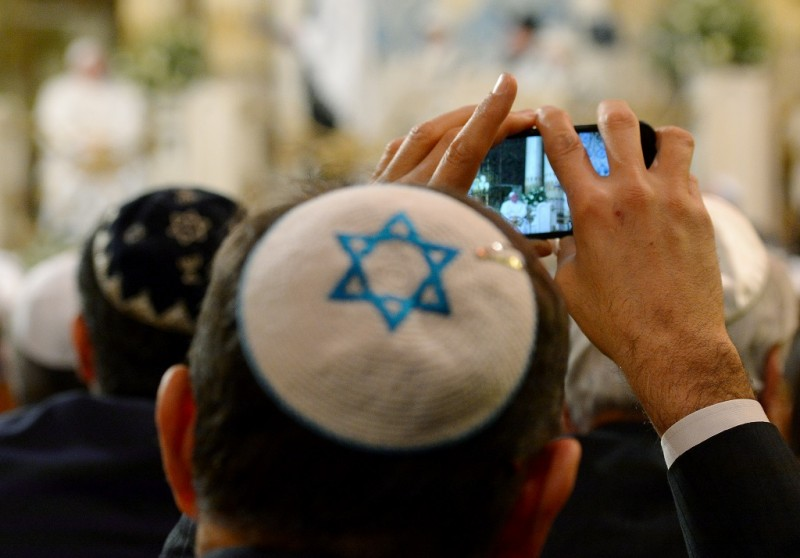 A member of the Rome's Jewish community takes pictures of Pope Francis during his visit in Rome's main Synagogue, on January 17, 2016. Pope Francis is the third pope to visit the synagogue and meet members of the Italian capital's Jewish community, after John-Paul II in 1986 and Benedict XVI in 2010. / AFP / VINCENZO PINTO