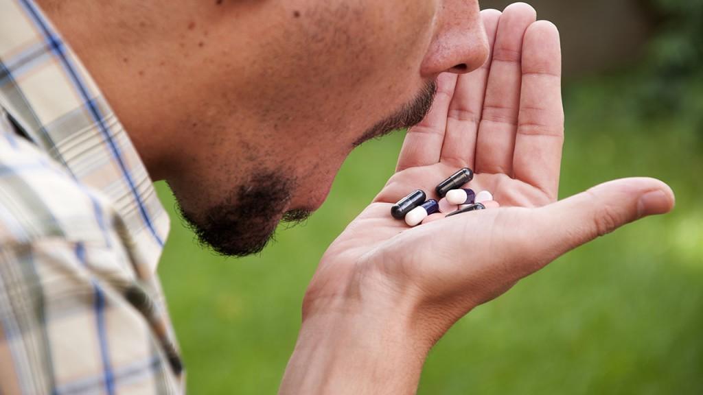 depressed man taking pills