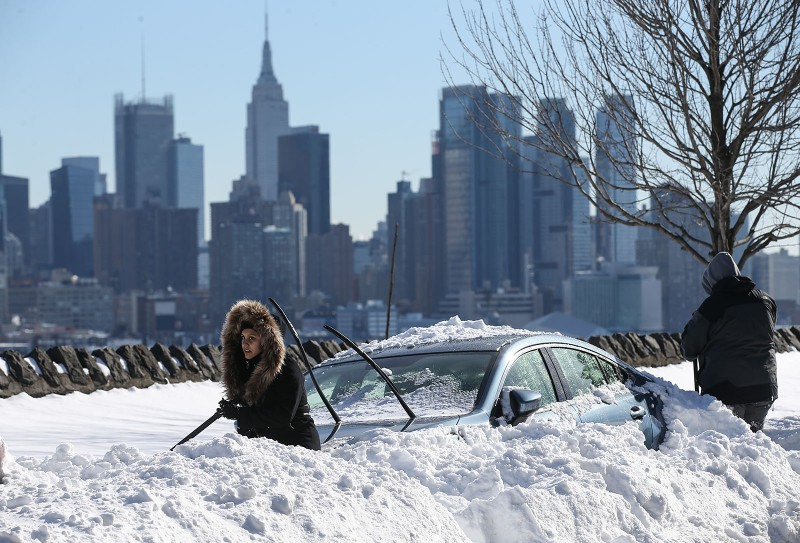 NEW YORK, USA - JANUARY 24:  Residents attempt to dig their cars out the snow in New York City, NY on January 24, 2016, after the winter storm Jonas hit New York and Washington. Cem Ozdel / Anadolu Agency