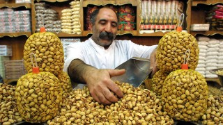 (FILES) -- A file picture dated December 21, 2001 shows an Iranian grocer displaying pistachios to a customer at his shop in Tehran.  Iran's pistachio production is set to plunge by 60 percent because of a winter freeze, allowing the United States to take over as the world's top exporter, an official was quoted as saying on September 9, 2008.  AFP PHOTO/BEHROUZ MEHRI / AFP / BEHROUZ MEHRI