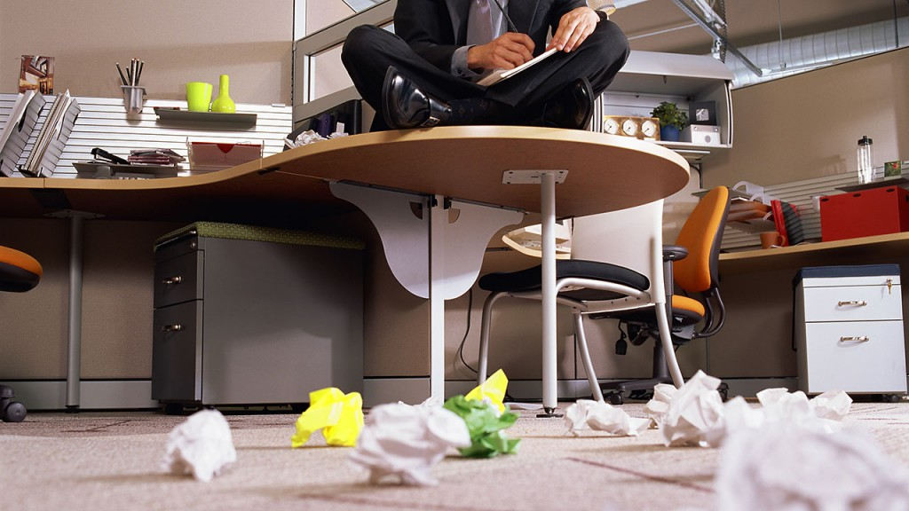 Businessman sitting on desk and crumpling paper