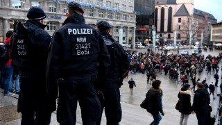 """Policemen look on as refugees from Syria demonstrate against violence near the Cologne main train station in Cologne, western Germany on January 16, 2016, where hundreds of women were groped and robbed in a throng of mostly Arab and North African men during New Year's festivities. German authorities said that nearly all the suspects in a rash of New Year's Eve violence against women in Cologne were """"of foreign origin"""", as foreigners came under attack amid surging tensions. / AFP / PATRIK STOLLARZ"""
