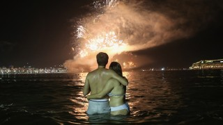RIO DE JANEIRO, BRAZIL - JANUARY 01:  Revellers embrace as fireworks explode to ring in the New Year above Copacabana beach on January 1, 2016 in Rio de Janeiro, Brazil. More than one million people were expected to gather on Copacabana beach to watch the fireworks display ringing in the New Year at midnight. The city is set to host the Rio 2016 Olympic Games in August.  (Photo by Mario Tama/Getty Images)