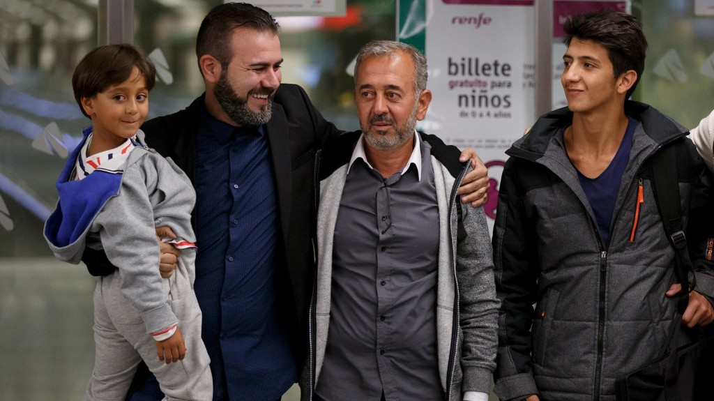MADRID, SPAIN - SEPTEMBER 16:  Syrian refugee Osama Abdul Mohsen (2R), his sons Mohamed 18 (R-L) and Zaid 7 (L) pose for the press with the President of Cenafe coaching schools Miguel Angel Galan at their arrival to Atocha Train Station on September 16, 2015 in Madrid, Spain. Syrian refugee Osama Abdul Mohsen was tripped up to the ground by Hungarian camerawoman Petra Laszlo while carrying his son seven years old Zaid as he was trying to cross from Serbia to Hungary chased by police. The images hit the headlines around the world. Mohsen and part of his family finally reached Germany and has now been offered a job as football coach in Getafe city in Spain for Cenafe.  (Photo by Pablo Blazquez Dominguez/Getty Images)
