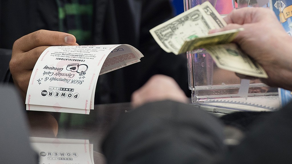 A man purchases a Powerball lottery ticket at a liquor store in Washington, DC, January 4, 2016. Lottery officials predict the January 6 jackpot will reach $400 million, one of the largest in the game's history. AFP PHOTO / SAUL LOEB / AFP / SAUL LOEB