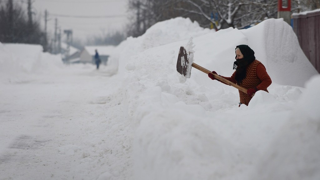 A woman shovels snow in the front of her house in Smeeni village near Bucharest on January 28, 2014. A thick blanket of snow covered southern and eastern Romania causing the closure of three highways, cancelling twenty rail links and disruptions in air traffic. AFP PHOTO / DANIEL MIHAILESCU / AFP / DANIEL MIHAILESCU