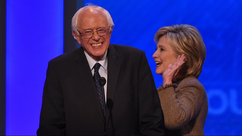 US Democratic presidential hopeful Hillary Clinton smiles as she walks past fellow candidate Bernie Sanders during a break of the Democratic Presidential Debate hosted by ABC News at the Saint Anselm College in Manchester, New Hampshire, on December 19, 2015. AFP PHOTO/JEWEL SAMAD / AFP / JEWEL SAMAD