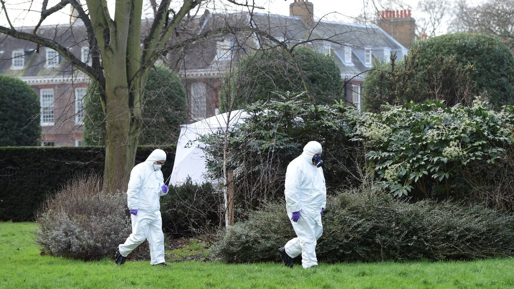 Forsensics officers in overalls and masks walk by the tent errected over the scene where a man died after being discovered on fire in the park outside the wall of Kensington Palace in London on February 9, 2016.   A man has died after being found on fire outside Kensington Palace in the early hours of February 9, police said. Officers were called to the London home of the Duke and Duchess of Cambridge after receiving reports a man was behaving suspiciously. On arrival a man was found on fire and despite efforts from officers and paramedics the man was pronouced dead at the scene.  / AFP / LEON NEAL