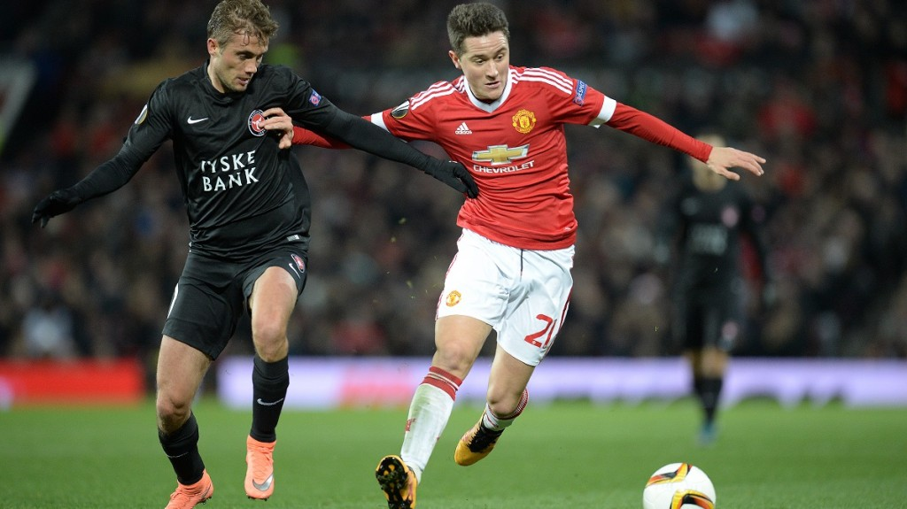 FC Midtjylland's Danish midfielder Jakob Poulsen (L) vies with Manchester United's Spanish midfielder Ander Herrera during the UEFA Europa League round of 32, second leg football match between Manchester United and and FC Midtjylland at Old Trafford in Manchester, north west England, on February 25, 2016.   / AFP / OLI SCARFF