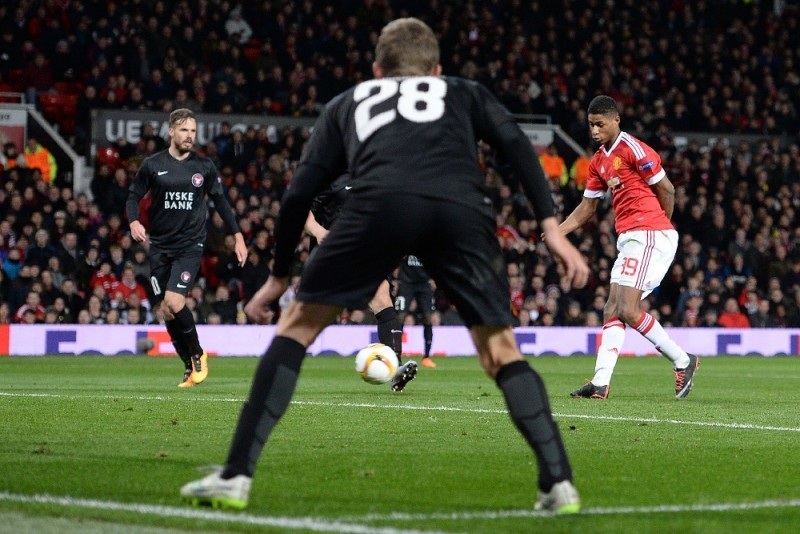 Manchester United's English striker Marcus Rashford (R) shoots to score his team's second goal during the UEFA Europa League round of 32, second leg football match between Manchester United and and FC Midtjylland at Old Trafford in Manchester, north west England, on February 25, 2016.   / AFP / OLI SCARFF