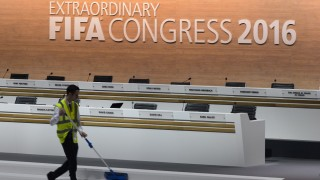 A worker cleans the stage during a break at the FIFA electoral congress on February 26, 2016 in Zurich. FIFA members will elect on February 26, 2016 a new president and pass reforms they hope will open an escape route from a storm of scandal symbolised by the downfall of veteran leader Sepp Blatter. / AFP / FABRICE COFFRINI