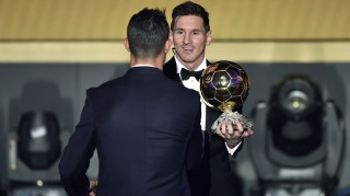 FC Barcelona and Argentina's forward Lionel Messi (R) holds his trophy as he shakes hands with Real Madrid and Portugal's forward  Cristiano Ronaldo after receiving the 2015 FIFA Ballon d'Or award for player of the year during the 2015 FIFA Ballon d'Or award ceremony at the Kongresshaus in Zurich on January 11, 2016. AFP PHOTO / FABRICE COFFRINI / AFP / FABRICE COFFRINI