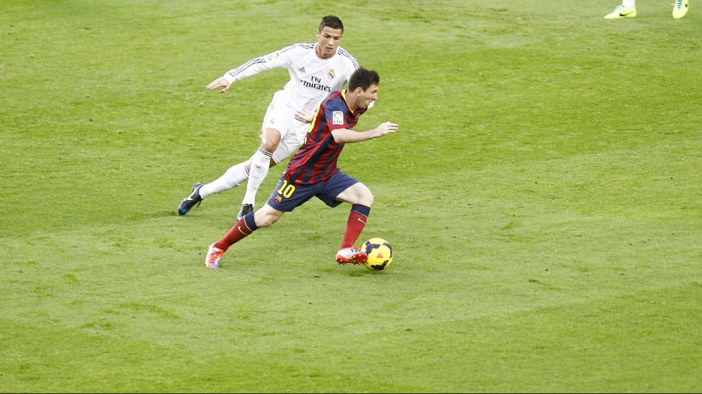 Barcelona's Argentinian forward Lionel Messi (R) vies with Real Madrid's Portuguese forward Cristiano Ronaldo during the Spanish league Clasico football match FC Barcelona vs Real Madrid CF at the Camp Nou stadium in Barcelona on October 26, 2013.   AFP PHOTO/ QUIQUE GARCIA / AFP / QUIQUE GARCIA