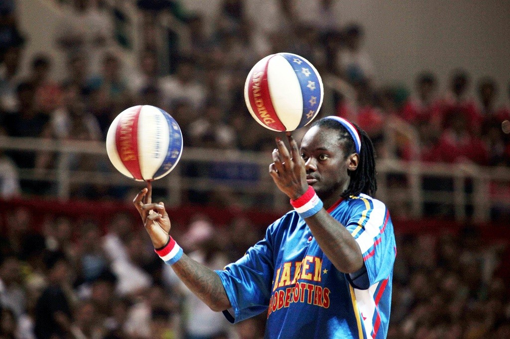 A player of Harlem Globetrotters, the famous American basketball team, shows his skill during the game held at the gymnasium of Xuchang Vocational Technical College in Xuchang, center Chinas Henan Province, 17 July, 2011.  American Harlem basketball team played a show game at the gymnasium of Xuchang Vocational Technical College on July 17, 2011.