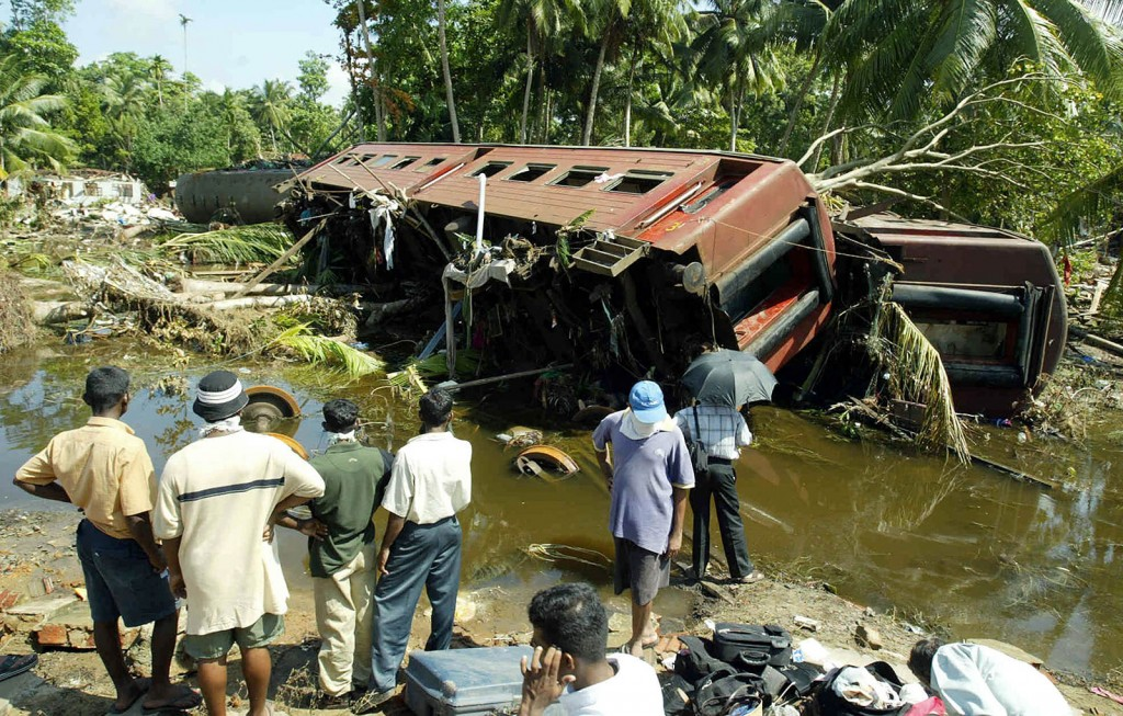 Sri Lankan villagers look at a derailed train coach in Sinigame, near the town of Hikaduwa on the southwestern coast of Sri Lanka 29 December 2004, after the train was swept away by quake-triggered tsunamis.  Sri Lanka Wednesday pressed its entire public service and the military into an unprecedented relief operation as it grappled with the magnitude of cleaning up after its worst disaster. Sunday's tsunamis which wiped out swathes of coastline killed at least 17,600 people in Sri Lanka alone.             AFP PHOTO / Jimin LAI / AFP / JIMIN LAI