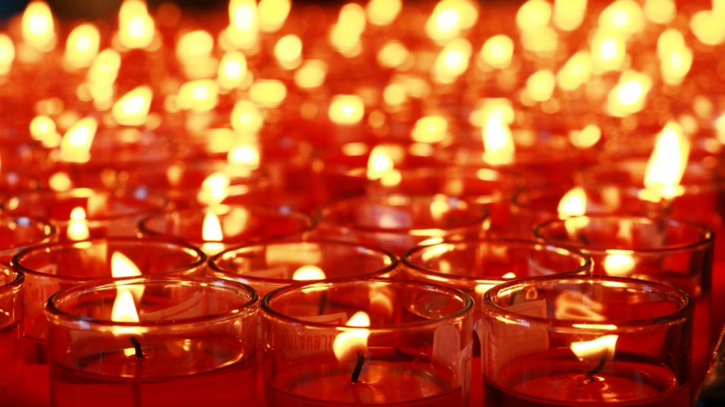 Many red candles burning at Buddhist temple interior