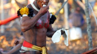 A Brazilian Kamayura Indian eats fish 14 August, 2005, before taking part in the Kuarup ceremony, in an area of the Amazon forest occupied by the Awara tribe, in central Brazil. The Kuarup ceremony is held around a wooden structure, ritually built to represent the spirits of the deceased. The first day of the ceremony is dedicated to honour the ancestors with elaborate rituals, while the second day is devoted to wrestling competitions.   AFP PHOTO/ANTONIO SCORZA / AFP / ANTONIO SCORZA