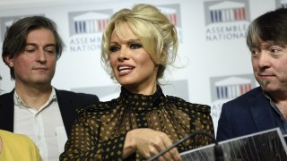 """US actress Pamela Anderson gives a press conference after attending a session of questions to the Government at the French National Assembly in Paris on January 19, 2016.  Former """"Baywatch"""" star Pamela Anderson set feathers flying in the French parliament when she turned up to support a ban on force-feeding ducks and geese to make foie gras / AFP / ERIC FEFERBERG"""