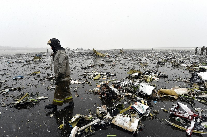 Russian emergency rescuer walks through wreckage of the flydubai passenger jet which crashed, killing all 62 people on board as it tried to land in bad weather in the city of Rostov-on-Don on March 19, 2016. The plane, which came from Dubai, was making its second attempt to land when it missed the runway, erupting in a huge fireball as it crashed, leaving debris scattered across a wide area. The ministry said more than 700 rescuers and 100 vehicles were combing the area in driving wind and snow where the wreckage was strewn, with investigators confirming one of the plane's black boxes had been retrieved.  / AFP / -