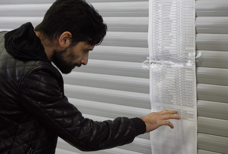 A man reads the passengers' list of the flydubai passenger jet that crashed, killing all 62 people on board in Rostov-on-Don on March 19, 2016. The plane, which came from Dubai, was making its second attempt to land when it missed the runway, erupting in a huge fireball as it crashed, leaving debris scattered across a wide area. The ministry said more than 700 rescuers and 100 vehicles were combing the area in driving wind and snow where the wreckage was strewn, with investigators confirming one of the plane's black boxes had been retrieved. / AFP / SERGEI VENYAVSKY
