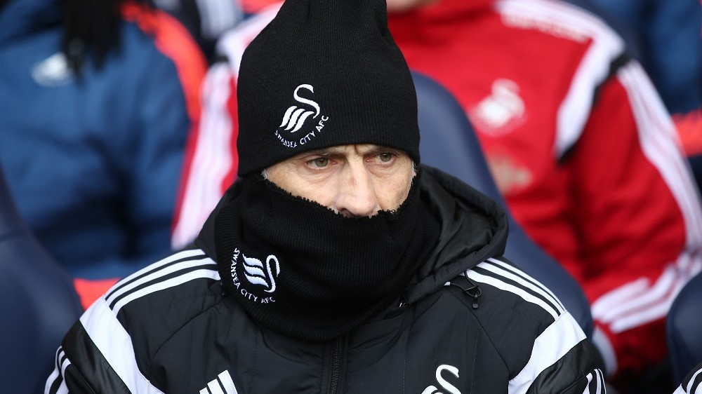 Swansea City's Italian head coach Francesco Guidolin is wrapped up against the cold ahead of the English Premier League football match between Tottenham Hotspur and Swansea City at White Hart Lane in London, on February 28, 2016. / AFP / JUSTIN TALLIS / RESTRICTED TO EDITORIAL USE. No use with unauthorized audio, video, data, fixture lists, club/league logos or 'live' services. Online in-match use limited to 75 images, no video emulation. No use in betting, games or single club/league/player publications.  /