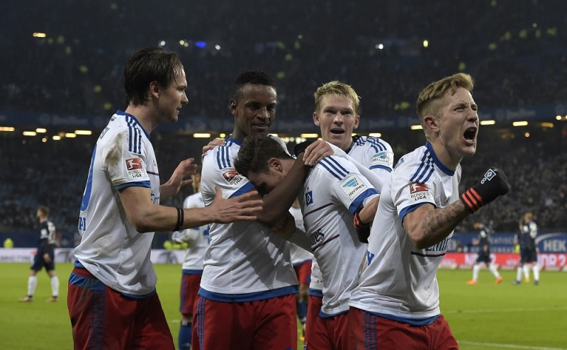 Hamburg's team players hug midfielder Nicolai Mueller (C) after scoring  during the German first division Bundesliga football match of Hamburger SV v Hertha BSC in Hamburg, on March 6, 2016. / AFP / TOBIAS SCHWARZ / RESTRICTIONS: DURING MATCH TIME: DFL RULES TO LIMIT THE ONLINE USAGE TO 15 PICTURES PER MATCH AND FORBID IMAGE SEQUENCES TO SIMULATE VIDEO. == RESTRICTED TO EDITORIAL USE == FOR FURTHER QUERIES PLEASE CONTACT DFL DIRECTLY AT + 49 69 650050