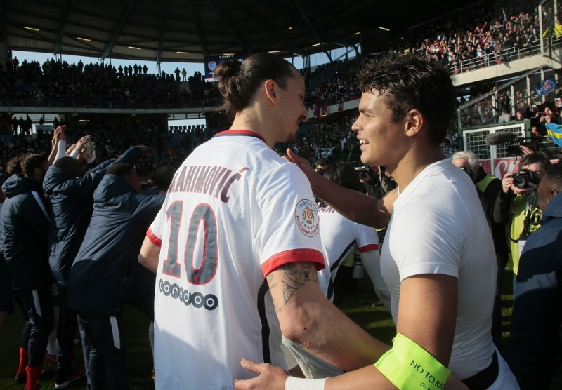 Paris Saint-Germain's Brazilian defender Thiago Silva (R) celebrates with Swedish forward Zlatan Ibrahimovic after winning the French Ligue 1 football match against Troyes to clinch a fourth consecutive Ligue 1 crown on March 13, 2016 at the Aube Stadium in Troyes. Paris Saint-Germain clinched a fourth consecutive Ligue 1 title in record time on March 13 after defeating Troyes, obliterating a new French record for the quickest league victory with eight games to spare before the end of the L1 championships. / AFP / JACQUES DEMARTHON