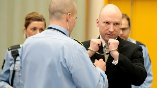 Norwegian mass killer Anders Behring Breivik (R) has his handcuffs removed inside the court room in Skien prison, March 16, 2016. Behring Breivik is charging Norwegian authorities of violating his human rights by holding him in isolation for almost five years. / AFP / NTB Scanpix / Lise Aserud / Norway OUT
