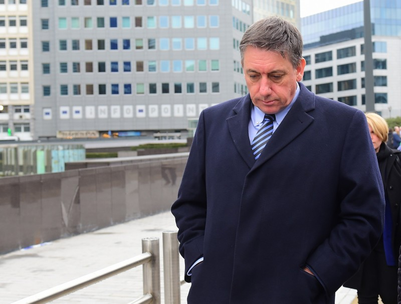 Belgium Interior Minister Jan Jambon arrives at the European Commission to take part in a ceremony in memory of the victims of Brussels' terror attacks on March 23, 2016 in Brussels.  / AFP / EMMANUEL DUNAND