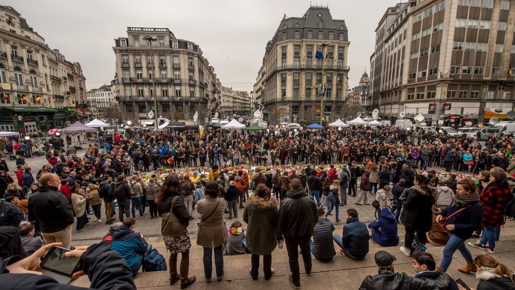 Belgians gather at a makeshift memorial at Place de la Bourse (Beursplein) in Brussels on March 24, 2016 as they hold a minute of silence for the victims of the terror attacks. A grieving Belgium hunted two fugitive suspects after bombings that struck at the very heart of Europe, as security authorities faced mounting criticism over the country's worst-ever attacks. / AFP / PHILIPPE HUGUEN