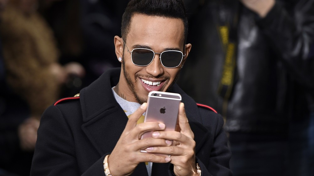 British driver Lewis Hamilton uses his mobile phone as he attends the John Galliano during the 2016-2017 fall/winter ready-to-wear collection on March 6, 2016 in Paris.  AFP PHOTO / MARTIN BUREAU / AFP / Martin BUREAU