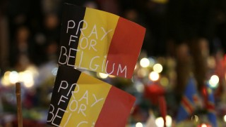 """Belgian flags reading """"Pray for Belgium"""" are pictured as people gather at a makeshift memorial on the Place de la Bourse (Beursplein) in Brussels on March 23, 2016, a day after a triple bomb attack, which responsibility was claimed by the Islamic State group, left 31 dead and hundreds injured in the Belgian capital. World leaders united in condemning the carnage in Brussels and vowed to combat terrorism, after Islamic State bombers killed 31 people in a strike at the symbolic heart of the EU. AFP PHOTO / KENZO TRIBOUILLARD / AFP / KENZO TRIBOUILLARD"""