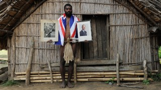 """TO GO WITH AFP STORY """"Vanuatu-Britain-religion-royals,FEATURE"""" by Madeleine Coorey Sikor Natuan, the son of the local chief, holds two official portraits (one holding a pig-killing club, L) of Britain's Prince Philip in front of the chief's hut in the remote village of Yaohnanen on Tanna in Vanuatu on August 6, 2010. In his remote village in Vanuatu, tribesman Sikor Natuan cradles a faded portrait of Britain's Prince Philip against his naked and tattooed chest. Natuan, who just weeks before danced and feasted to mark the royal's 89th birthday, is already preparing for next year's celebrations -- and he is expecting the guest of honour to attend, despite his advanced age. For in the South Pacific village of Yaohnanen on Vanuatu's Tanna island, where men wear nothing but grass penis sheaths, and marijuana and tobacco grow wild, Prince Philip is worshipped as a god.  AFP PHOTO / Torsten BLACKWOOD / AFP / TORSTEN BLACKWOOD"""