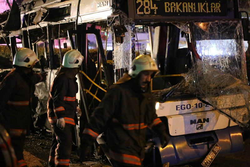 Rescuers walk by the wreckage of a bus at the scene of a blast in Ankara on March 13, 2016.