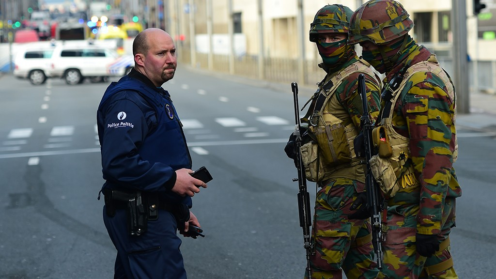 Policemen and soldier stand guard at the entrance of a security perimeter set near Maalbeek metro station,  on March 22, 2016  in Brussels, after a blast at this station near the EU institutions caused deaths and injuries.  AFP PHOTO / EMMANUEL DUNAND / AFP / EMMANUEL DUNAND