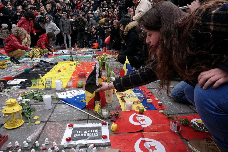People gather to observe a minute of silence in memory of the victims of the Brussels airport and metro bombings, on the Place de la Bourse in central Brussels, on March 23, 2016, a day after the triple blasts killed some 30 people and left around 250 injured.World leaders united in condemning the carnage in Brussels and vowed to combat terrorism, after Islamic State bombers killed around 35 people in a strike at the symbolic heart of the EU. / AFP / PATRIK STOLLARZ