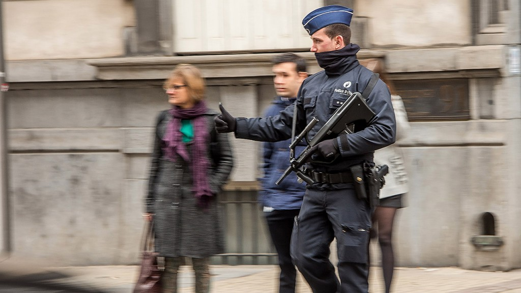 A police officer stops traffic to let pedestrians cross a street during a patrol in Brussels on March 24, 2016, two days after terror attacks hit the Belgian capital.More than 30 people have been identified as being involved in a network behind the Paris attacks on November 13, with links now established to this week's bombings in Brussels. / AFP / PHILIPPE HUGUEN