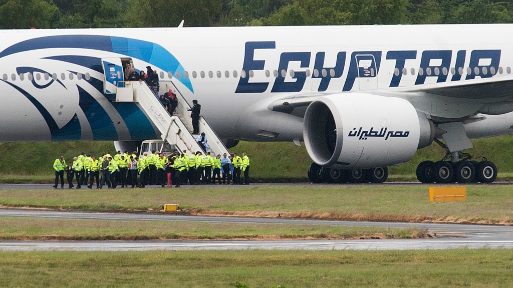 """Police escort passengers off the Egyptair Boeing 777 flight from Cairo that was forced to land at Glasgow Prestwick airport in Scotland on June 15, 2013 en route to JFK airport in New York after an onboard incident. Britain's Royal Air Force (RAF) on June 15 escorted an Egyptair plane bound for New York to a Scottish airport following an onboard incident, the Ministry of Defence said. The Boeing 777 was travelling between Cairo and New York when a passenger alerted plane crew that she had found a note reading """"I'll set this plane on fire"""" in the toilet. The message was scrawled in pencil on a napkin and was found by BBC New York producer Nada Tawfik. AFP PHOTO / ANDY BUCHANAN / AFP / Andy Buchanan"""